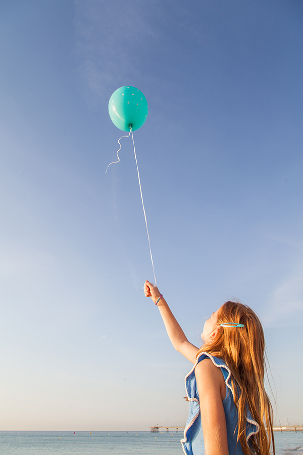 Elisa sostiene un globo y mira al cielo.